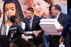 David L. Cohen and Jeremy Ford distribute free Dell laptops to children.