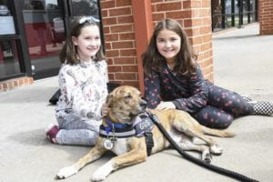 Two children sit with a service dog