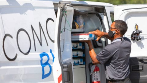 A Comcast technician unloads supplies from a van